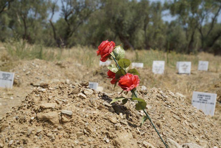 Eines der schlichten Gräber ist mit einer Plastikrose geschmückt